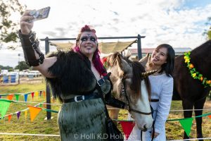 A woman in viking costume taking a selfie with a unicorn