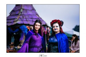 Two women in fantasy costumes in front of a witch hut