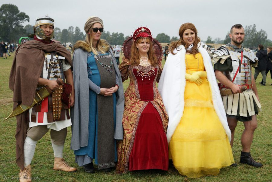Three women dressed in medieval and princess costumes are between two men in roman uniforms.